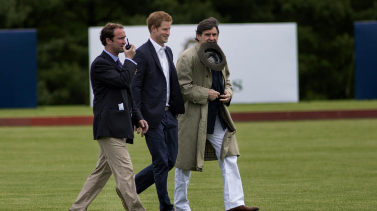 Britain's Prince Harry walks across the polo field before the Sentebale Royal Salute Polo Cup charity match in Greenwich, Conn., Wednesday, 15, 2103. Right is Peter Brant, founder of the Greenwich Polo Club. (AP Photo/Craig Ruttle)