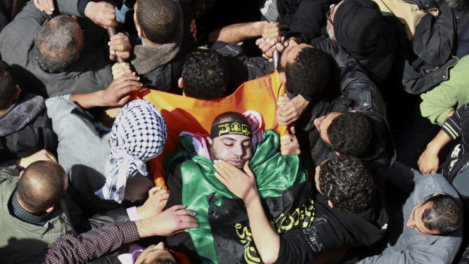 Palestinians carry the body of Islamic Jihad militant Ahmad Hajaj during his funeral in Gaza City, Saturday, March 10, 2012. The worst violence between Israel and the Gaza Strip in nearly a year entered its second day on Saturday, as Israeli aircraft killed 14 militants, according to Palestinian health officials. Militants responded by firing nearly 100 rockets, seriously wounding an Israeli civilian. (AP Photo/Adel Hana)