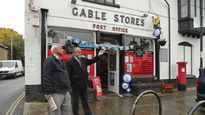 Men chat outside Harmondsworth Post Office in Harmondsworth, north of Heathrow airport in West London