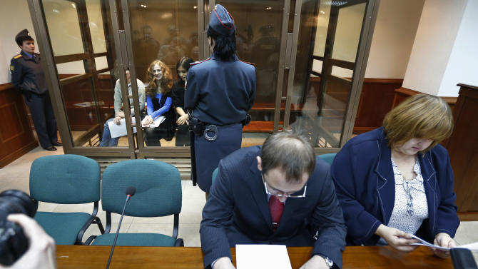 CORRECTS LEFT TO RIGHT Feminist punk group Pussy Riot members, from left, Yekaterina Samutsevich, Maria Alekhina, and Nadezhda Tolokonnikova sit in a glass cage at a court room in in Moscow, Wednesday Oct. 10, 2012. Lawyers Violetta Volkova, right, and Lev Lyalin, foreground center, defending members of feminist punk group Pussy Riot, sit in front. (AP Photo/Sergey Ponomarev)