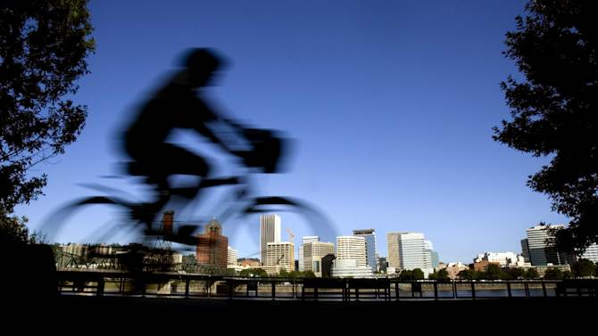 """FILE - In this July 10, 2008 file photo, a bicyclist is a blur traveling along the east bank of the Willamette River as the downtown skyline is bathed in early morning sunlight in Portland, Ore. A famous quip by Fred Armisen on the television show """"Portlandia"""" led Portland State University researchers to investigate the reality behind the comment. The quirky IFC network series pokes fun at the Oregon city's many eccentricities. (AP Photo/Don Ryan, File)"""