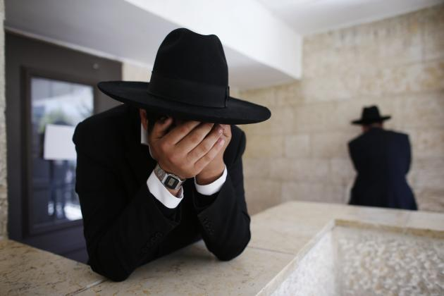 Ultra-Orthodox Jewish men react upon hearing the news about the death of Rabbi Yosef in Jerusalem