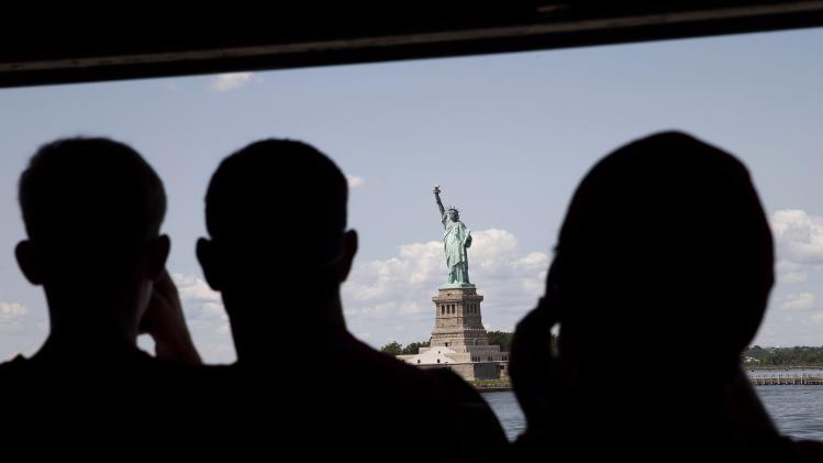 Tourists view the Statue of Liberty from the Staten Island Ferry on a clear and cool day in New York Harbor