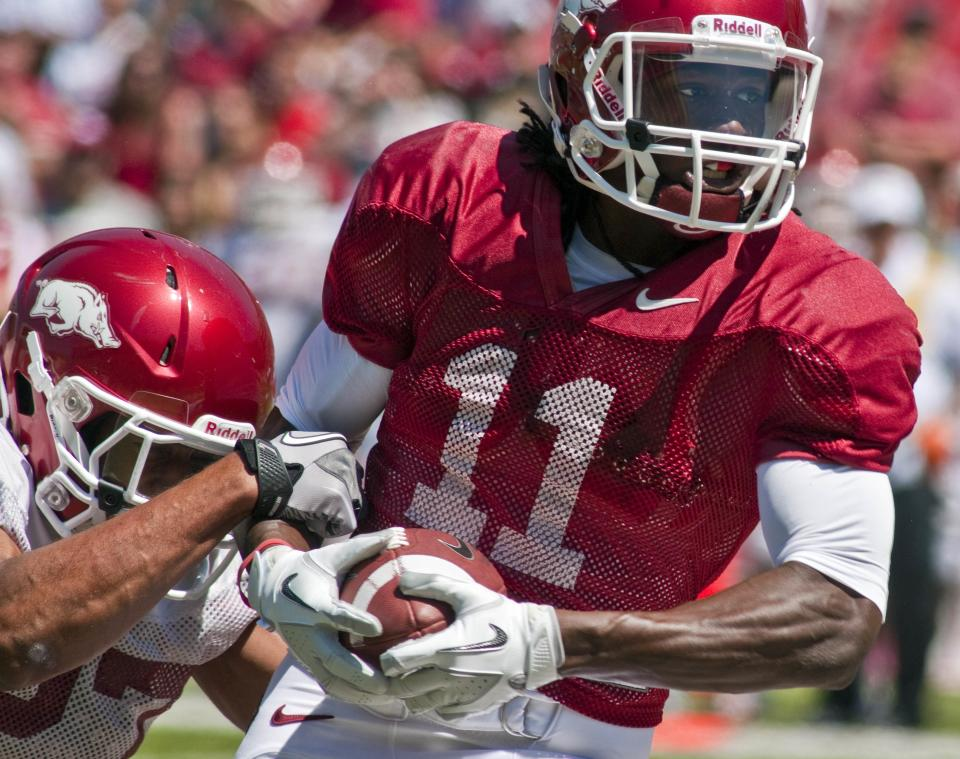 Arkansas red team receiver Cobi Hamilton (11) tries to break the tackle of white team safety Alan Turner, left, after making a catch during the first quarter of a spring NCAA college football game in Fayetteville, Ark., Saturday, April 21, 2012. (AP Photo/April L. Brown)