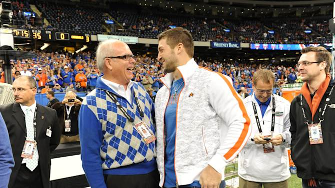 IMAGE DISTRIBUTED FOR ALLSTATE- University of Florida president Bernie Machen (left) and former Gators quarterback Tim Tebow (right) at the 2013 Allstate Sugar Bowl in New Orleans on Jan. 2, 2013.  The Louisville  Cardinals beat Florida, 33-23, in the 79th annual bowl game. (Cheryl Gerber/AP Images for Allstate)