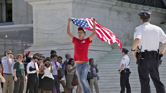 A gay rights activist runs out of the Supreme Court in Washington, Wednesday, June 26, 2013, as rulings were handed down that impact same-sex relationships. In two separate and significant victories for gay rights, the Supreme Court struck down a provision of a federal law denying federal benefits to married gay couples and cleared the way for the resumption of same-sex marriage in California. (AP Photo/J. Scott Applewhite)