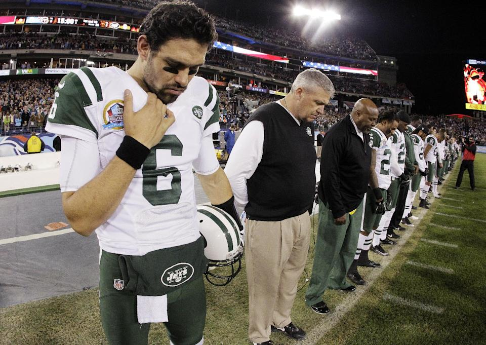 New York Jets quarterback Mark Sanchez (6) and head coach Rex Ryan bow their heads during a moment of silence for the victims of the Sandy Hook Elementary School shootings in Newtown, Conn., before an NFL football game against the Tennessee Titans, Monday, Dec. 17, 2012, in Nashville, Tenn. (AP Photo/Wade Payne)