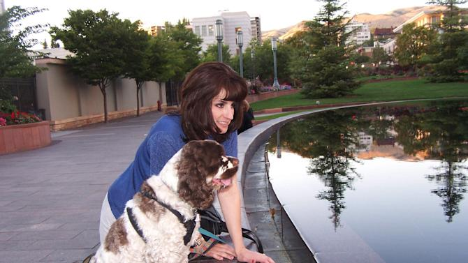 This undated photo shows Carol Bryant of Forty Fort, Pa., and her cocker spaniel, Dexter, at Salt Lake City Temple during the BlogPaws conference in Salt Lake City, Utah. Dexter travels the country with Bryant, a blogger who spends her time meeting other pet owners. Dexter often breaks the ice because he knows no strangers and even has his own business cards. (AP Photo/Carol Bryant, Darlene Bryant)