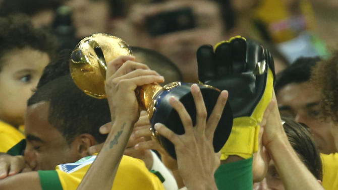Brazil's Neymar, center, lifts the trophy after winning the soccer Confederations Cup final between Brazil and Spain at the Maracana stadium in Rio de Janeiro, Brazil, Sunday, June 30, 2013. (AP Photo/Bruno Magalhaes)