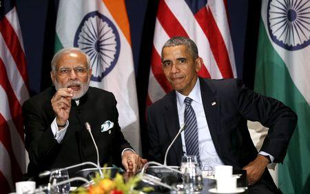 U.S. President Obama and Indian Prime Minister Modi clasp hands while meeting at the climate change summit in Paris