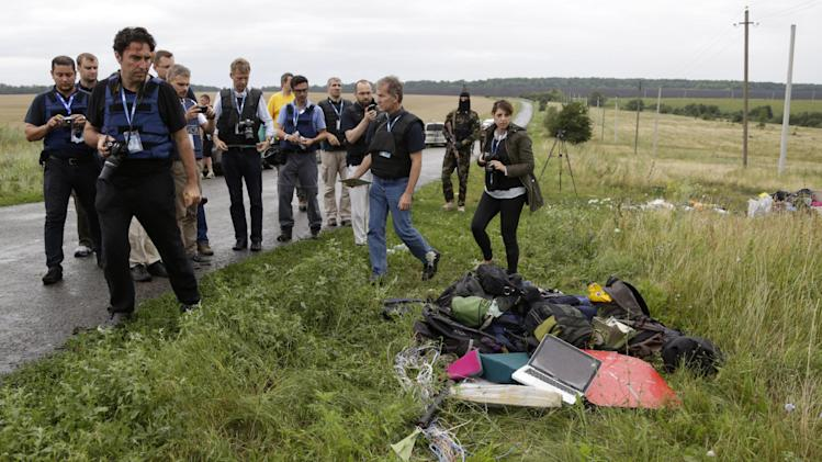Representatives from the OSCE (Organization for Security and Co-operation in Europe) delegation inspect passengers' personal luggage collected at the site of a crashed Malaysia Airlines passenger plane near the village of Hrabove, Ukraine, eastern Ukraine Friday, July 18, 2014. Rescue workers, policemen and even off-duty coal miners were combing a sprawling area in eastern Ukraine near the Russian border where the Malaysian plane ended up in burning pieces Thursday, killing all 298 aboard. (AP Photo/Dmitry Lovetsky)