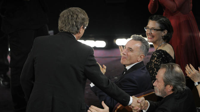 """From right, Tommy Lee Jones and Daniel Day Lewis congratulate Rick Carter as Carter walks on stage to accept the award for best production design for """"Lincoln"""" during the Oscars at the Dolby Theatre on Sunday Feb. 24, 2013, in Los Angeles.  (Photo by Chris Pizzello/Invision/AP)"""