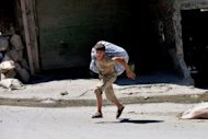 A Syrian youth runs to escape the Al Mashad neighbourhood during clashes between rebel fighters and government forces in the northern city of Aleppo on August 25. Syrian President Bashar al-Assad said on Sunday the foreign &quot;conspiracy&quot; against his country would be defeated, as his forces were accused of a bloody rampage