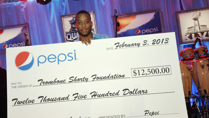 IMAGE DISTRIBUTED FOR PEPSI - Trombone Shorty accepts a check from Pepsi to the Trombone Shorty Foundation at the Pepsi 5th Quarter in the French Quarter Post Super Bowl Party, on Sunday, Feb. 3, 2013, in New Orleans. (Photo by Jack Dempsey/Invision for Pepsi/AP Images)