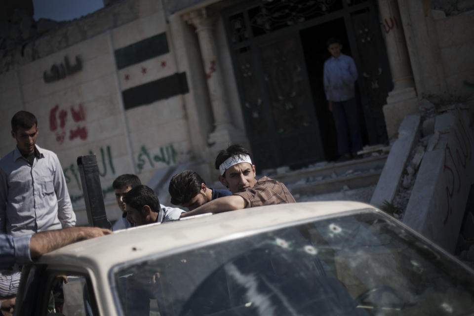 In this Sunday, Sept. 23, 2012 photo, Free Syrian Army fighters are seen in a truck outside their headquarters in Aleppo, Syria. (AP Photo/ Manu Brabo)