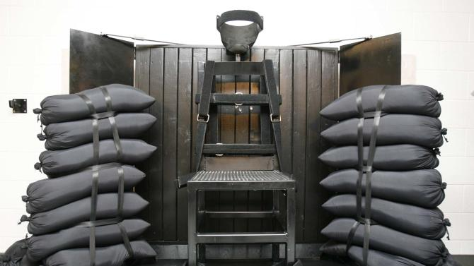 FILE - This June 18, 2010 file photo shows the execution chamber at the Utah State Prison after Ronnie Lee Gardner was executed by firing squad in Draper, Utah. The bullet holes are visible in the wood panel behind the chair. Gardner was convicted of aggravated murder, a capital felony, in 1985. America's executions have changed dramatically over the years, morphing from day-long events in the town square to somber and tightly controlled affairs held deep inside prisons. (AP Photo/Trent Nelson, Pool, File)