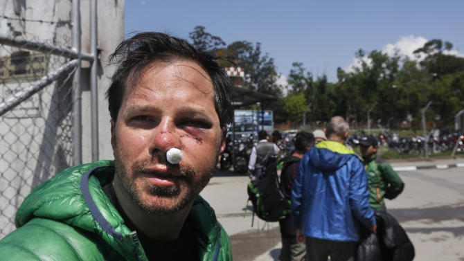 U.S. citizen Michael Churton, 38, from New York, who was injured during an avalanche resulting from Saturday's earthquake at the base camp of the mount Everest, arrives at the domestic airport in Kathmandu, Nepal, Monday, April 27, 2015. Saturday's magnitude 7.8 earthquake spread horror from Kathmandu to small villages and to the slopes of Mount Everest, triggering an avalanche that buried part of the base camp packed with foreign climbers preparing to make their summit attempts. (AP Photo / Manish Swarup)