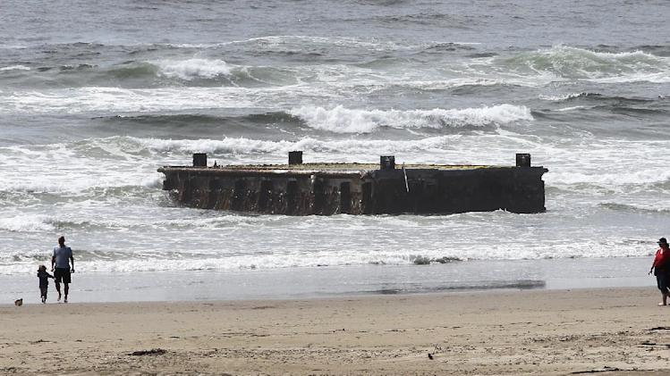 People walk along the beach near the massive dock that washed ashore on Agate Beach Wednesday, June 6, 2012, in Newport, Ore.  A nearly 70-foot-long dock that floated ashore on an Oregon beach was torn loose from a fishing port in northern Japan by last year's tsunami and drifted across thousands of miles of Pacific Ocean, a Japanese Consulate official said Wednesday.  (AP Photo/Rick Bowmer)