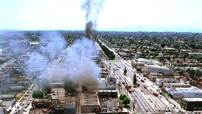FILE - Smoke covers Los Angeles in this Thursday, April 30, 1992 file photo as fires like this one on Vermont Avenue burn out of control. The worst riots in modern U.S. history began when outnumbered police were faced down by a crowd angered by the acquittals of four white police officers accused in the videotaped beating of black motorist Rodney King. (AP Photo/Paul Sakuma, File)