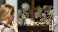 A foreign tourist looks at skulls of Khmer Rouge's victims displayed at the site of the former killing fields in Choeung Ek. The discovery of more than 1,200 photographs of former prisoners at a notorious Khmer Rouge torture jail has raised hopes that more Cambodians could learn their relatives' fate, researchers said Thursday