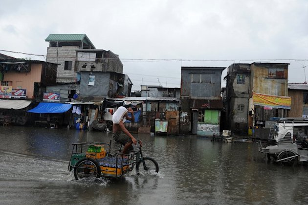 A man on his bike wades through a flooded street in Manila on June 30, 2013. Fresh flooding paralysed parts of the capital on Monday after heavy rain overnight from Tropical Storm Trami