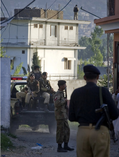 Pakistan army soldiers and a police officer patrol past the house, background, where it is believed al-Qaida leader Osama bin Laden lived in Abbottabad, Pakistan on Monday, May 2, 2011. Bin Laden, the
