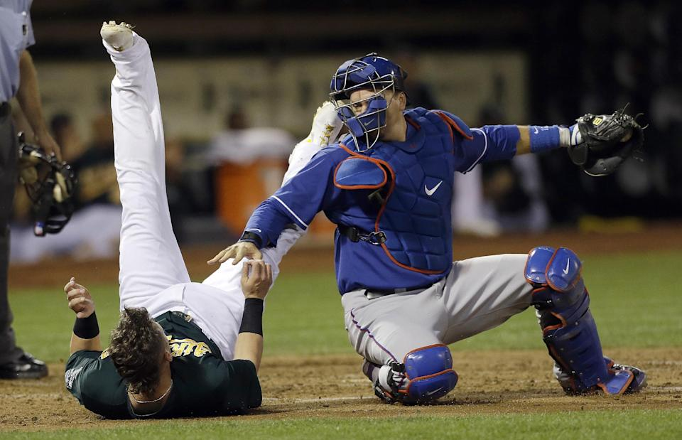 Texas Rangers catcher A.J. Pierzynski, right, reaches toward Oakland Athletics' Josh Donaldson after tagging him out at home plate during the third inning of a baseball game in Oakland, Calif., Tuesday, Sept. 3, 2013. (AP Photo/Jeff Chiu)