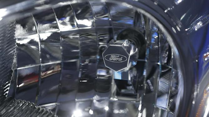 A headlight with a Ford logo is shown on the Ford Transit van at the North American International Auto Show in Detroit, Tuesday, Jan. 15, 2013. (AP Photo/Carlos Osorio)