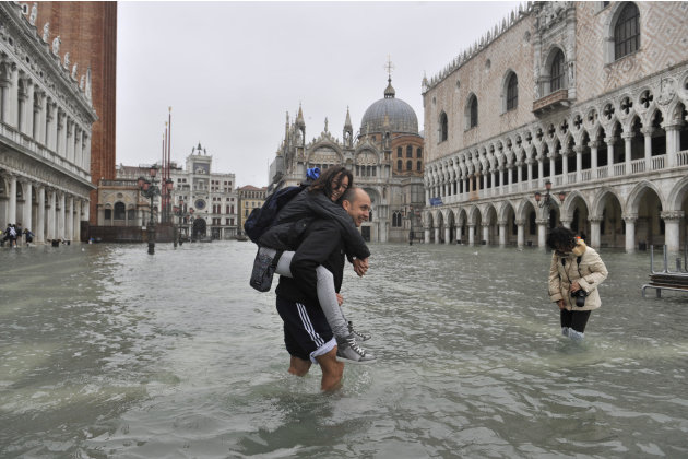 People cross flooded St. Mark's Square in Venice, Italy, Thursday, Nov. 1, 2012. High tides have flooded Venice, leading Venetians and tourists to don high boots and use wooden walkways to cross St. M