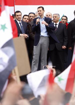 Syrian President Bashar Assad, center, addresses supporters during a rally at a central square in Damascus, Syria, Wednesday, Jan. 11, 2012. Assad joined thousands of his supporters Wednesday in an extremely rare public appearance at a rally in the capital Damascus, telling the crowd he wanted to draw strength from them. (AP Photo/Muzaffar Salman)