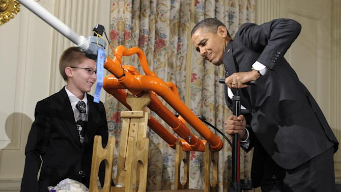 President Barack Obama pumps up a gun designed by Joey Hudy, left, of Phoenix, Ariz., left,  to shoot a marshmallow in the State Dining Room of the White House in Washington, Tuesday, Feb. 7, 2012, during the White House Science Fair. Obama hosted the second White House Science Fair celebrating the student winners of a broad range of science, technology, engineering and math (STEM) competitions from across the country. (AP Photo/Susan Walsh)