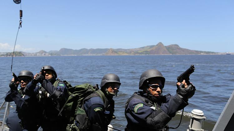 "CORRECTS WEDNESDAY TO THURSDAY - Brazilian Marines practice raiding a ship during a military exercise in Guanabara Bay, in Rio de Janeiro, Brazil, Thursday, Feb. 20 2014. Brazil's Navy said that the operations being carried out this week in preparation for the 2014 FIFA World Cup are the largest exercises in its history. FIFA director of security Ralf Mutschke has said that FIFA is satisfied with the level of security that will be provided by Brazilian authorities, and guarantees that football's governing body ""is highly committed to ensuring the safety and security for fans, players and any other stakeholder involved in our event."" (AP Photo/Leo Correa)"