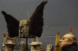 A man looks at an antique tribal Tumas Crow Mother mask displayed at athe Drouot auction house in Paris