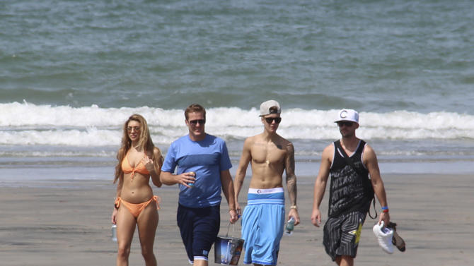 Justin Bieber, second right, and Chantel Jeffries, far left, walk with unidentified people on a beach in Punta Chame, Panama, Saturday, Jan. 25, 2014. A Panamanian radio and television host says trouble-plagued pop star Justin Bieber has been relaxing on a beach in Panama on a vacation from the United States. Eddy Vasquez was filming a show at the Pacific Coast resort in Punta Chame, about 90 miles west of Panama City, when he spotted Bieber and members of his entourage walking along the beach. (AP Photo/Eddy Vasquez)