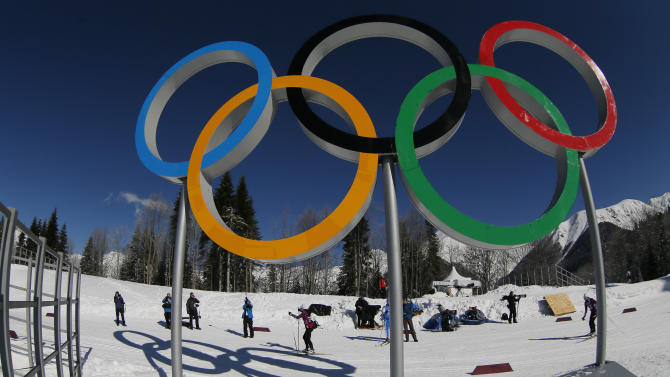 Cross country skiers pass by the Olympic rings prior to the 2014 Winter Olympics, Wednesday, Feb. 5, 2014, in Krasnaya Polyana, Russia. (AP Photo/Dmitry Lovetsky)