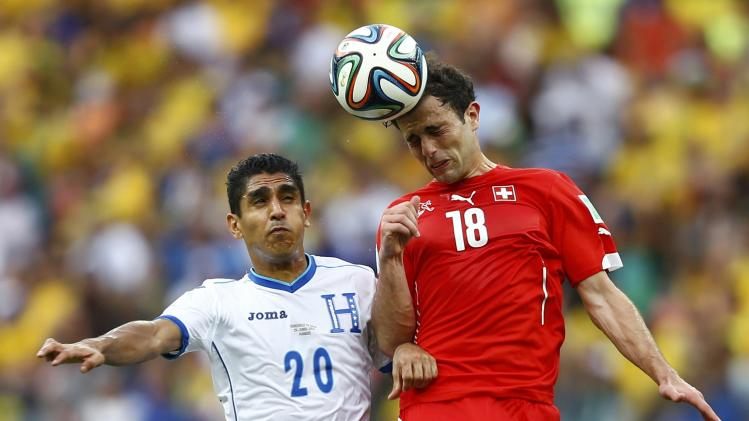 Switzerland's Admir Mehmedi fights for the ball with Jorge Claros of Honduras during their 2014 World Cup Group E soccer match at the Amazonia arena in Manaus