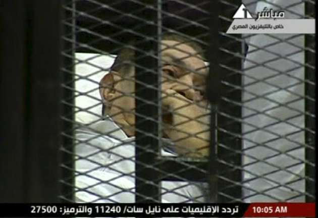Hosni Mubarak laying on a hospital bed inside a cage of mesh and iron bars in a Cairo courtroom Wednesday. (AP Photo/Egyptian State TV)
