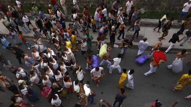 "Models are followed by the public as they perform Cuban artist Manuel Mendive's creation ""Scape"" during the 12th Havana Biennial, in Havana"