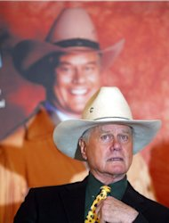 FILE - In this Wednesday, Feb. 19, 2003 file photo, actor Larry Hagman sits in front of a poster of himself during a news conference in Berlin during a tour to promote the German translation of his autobiography. Actor Larry Hagman, who for more than a decade played villainous patriarch JR Ewing in the TV soap Dallas, has died at the age of 81, his family said Saturday Nov. 24, 2012. (AP Photo/Markus Schreiber)
