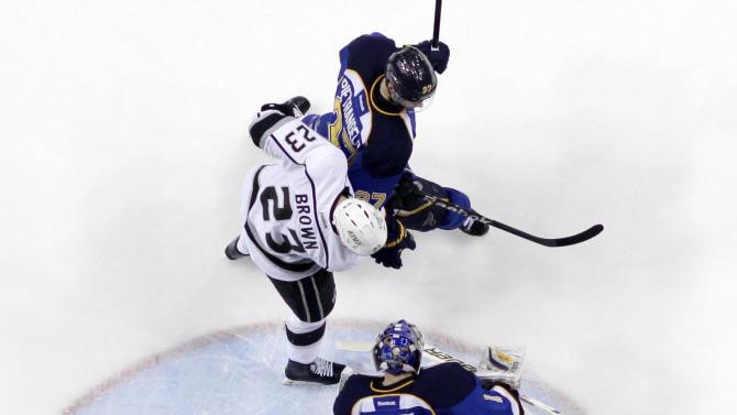 Los Angeles Kings' Dustin Brown (23) deflects in a puck to score past St. Louis Blues goalie Brian Elliott, bottom, and Alex Pietrangelo during the first period in Game 2 of a first-round NHL hockey Stanley Cup playoff series on Thursday, May 2, 2013, in St. Louis. (AP Photo/Jeff Roberson)