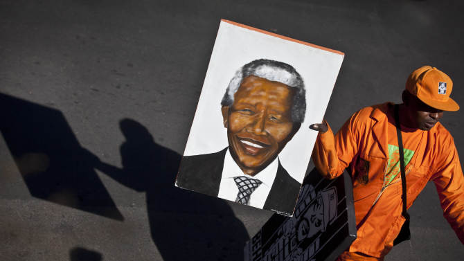An arriving wellwisher carries a portrait of Nelson Mandela as he walks down the street outside the entrance to the Mediclinic Heart Hospital where former South African President Nelson Mandela is being treated in Pretoria, South Africa Thursday, June 27, 2013. Makaziwe Mandela, daughter of Nelson Mandela, said Thursday he is in very critical condition but is still opening his eyes and reacting to touch at the South African hospital where he is being treated. (AP Photo/Ben Curtis)