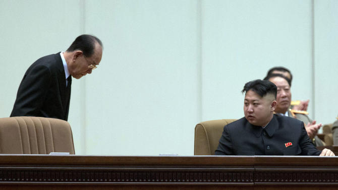 North Korea's President of the Presidium of the Supreme People's Assembly Kim Yong Nam, left, bows to North Korean leader Kim Jong Un during a national meeting of top party and military officials on the eve of the first death anniversary of Kim Jong Un's father Kim Jong Il in Pyongyang, North Korea, Sunday, Dec. 16, 2012. (AP Photo/Ng Han Guan)