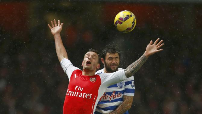 Arsenal's Mathieu Debuchy is challenged by Queens Park Rangers' Charlie Austin at the Emirates Stadium in London