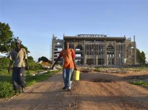 Workers walk in front of construction site of new building housing the administrative headquarters for the Kenya Ports Authority in Lamu
