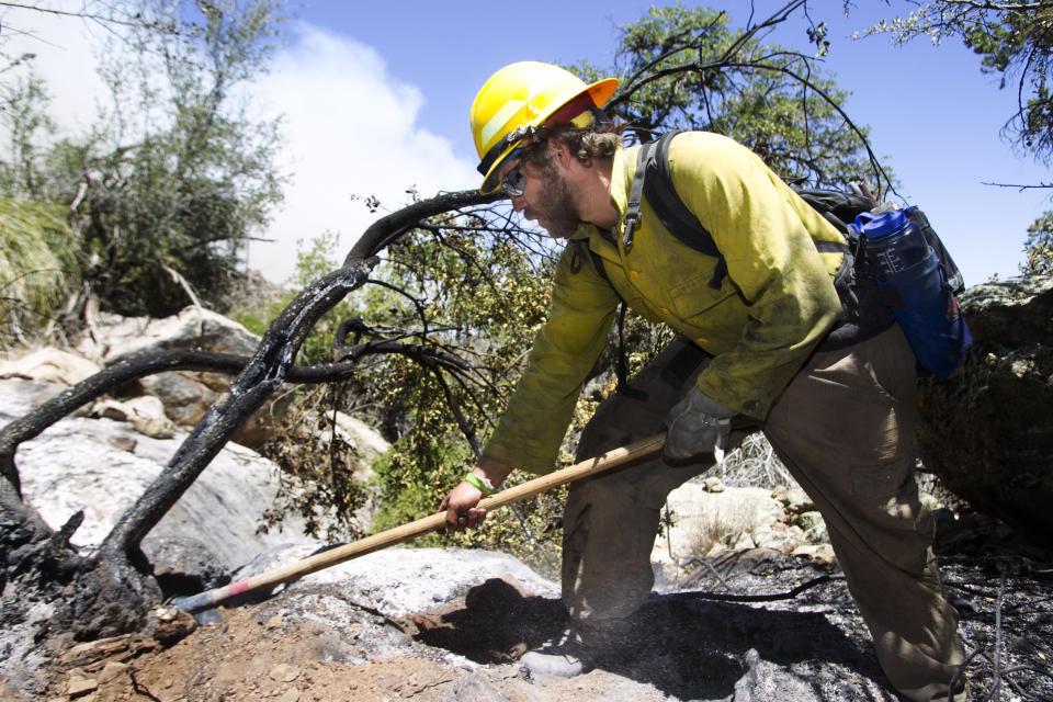 Ian Johnson,  a Bureau of Land Management firefighter mops up hot spots as thewild fire burns in the Bradshaw Mountains in the Prescott National Forest, Ariz.  on Wednesday, May 16, 2012. (AP Photo/The Arizona Republic, David Wallace)  MARICOPA COUNTY OUT; MAGS OUT; NO SALES
