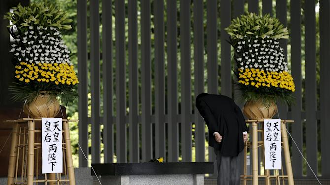 Japan's PM Abe bows as he offers a flower for Japan's unidentified war dead, during a ceremony at Chidorigafuchi National Cemetery in Tokyo