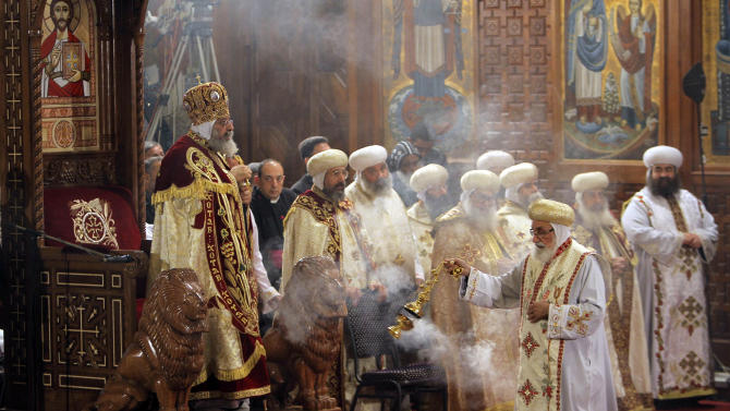 Pope Tawadros II, the 118th pope of the Coptic Church of Egypt, left, leads a midnight Mass on the eve of Orthodox Christmas at St. Mark's Cathedral in Cairo, Egypt, late Sunday Jan. 6, 2013. (AP Photo/Amr Nabil)