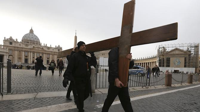People carry a wooden cross after praying in St. Peter's Square, at the Vatican, Monday, Feb. 25, 2013. Pope Benedict XVI has changed the rules of the conclave that will elect his successor, allowing cardinals to move up the start date if all of them arrive in Rome before the usual 15-day transition between pontificates. Benedict signed a legal document, issued Monday, with some line-by-line changes to the 1996 Vatican law governing the election of a new pope. It is one of his last acts as pope before resigning Thursday. (AP Photo/Dmitry Lovetsky)