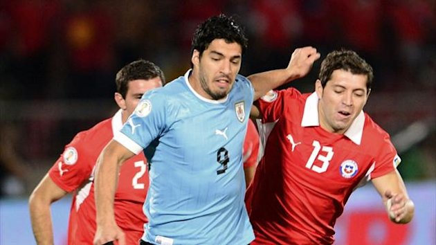 Uruguay's Luis Suarez (C) is followed by Chile's Eugenio Mena (L) and Jose Manuel Rojas during their World Cup South American qualifier (AFP)