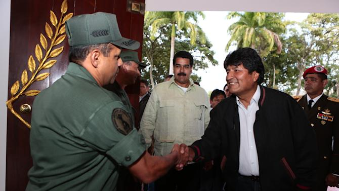 In this photo provided by Miraflores Presidential Press Office, Bolivia's President Evo Morales, right, shakes hands with a National Guard soldier, left, upon his arrival to the Military Academy in Caracas, Venezuela, Tuesday, Feb. 19, 2013. Morales is in Venezuela to visit Venezuela's President Hugo Chavez, whose sudden return to his country after more than two months of cancer treatments in Cuba has fanned speculation that the president could be preparing to relinquish power and make way for a successor and a new election. At center, Venezuela's Vice President Nicolas Maduro. (AP Photo/Miraflores Presidential Office)